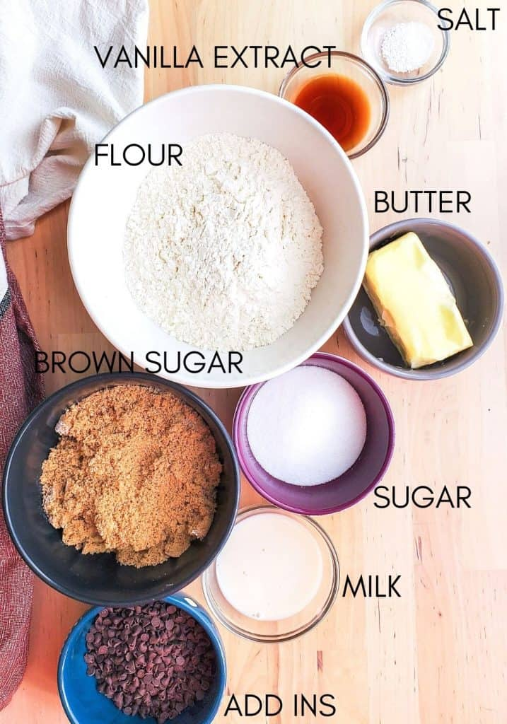 Overhead shot of cookie dough ingredients in small bowls with names in black text.