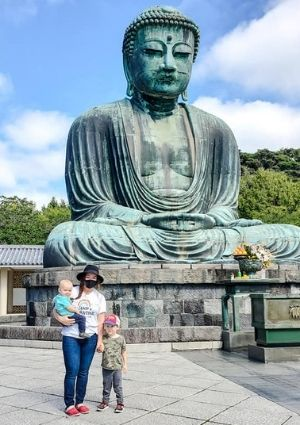 Mom with two son in front of buddha statue.