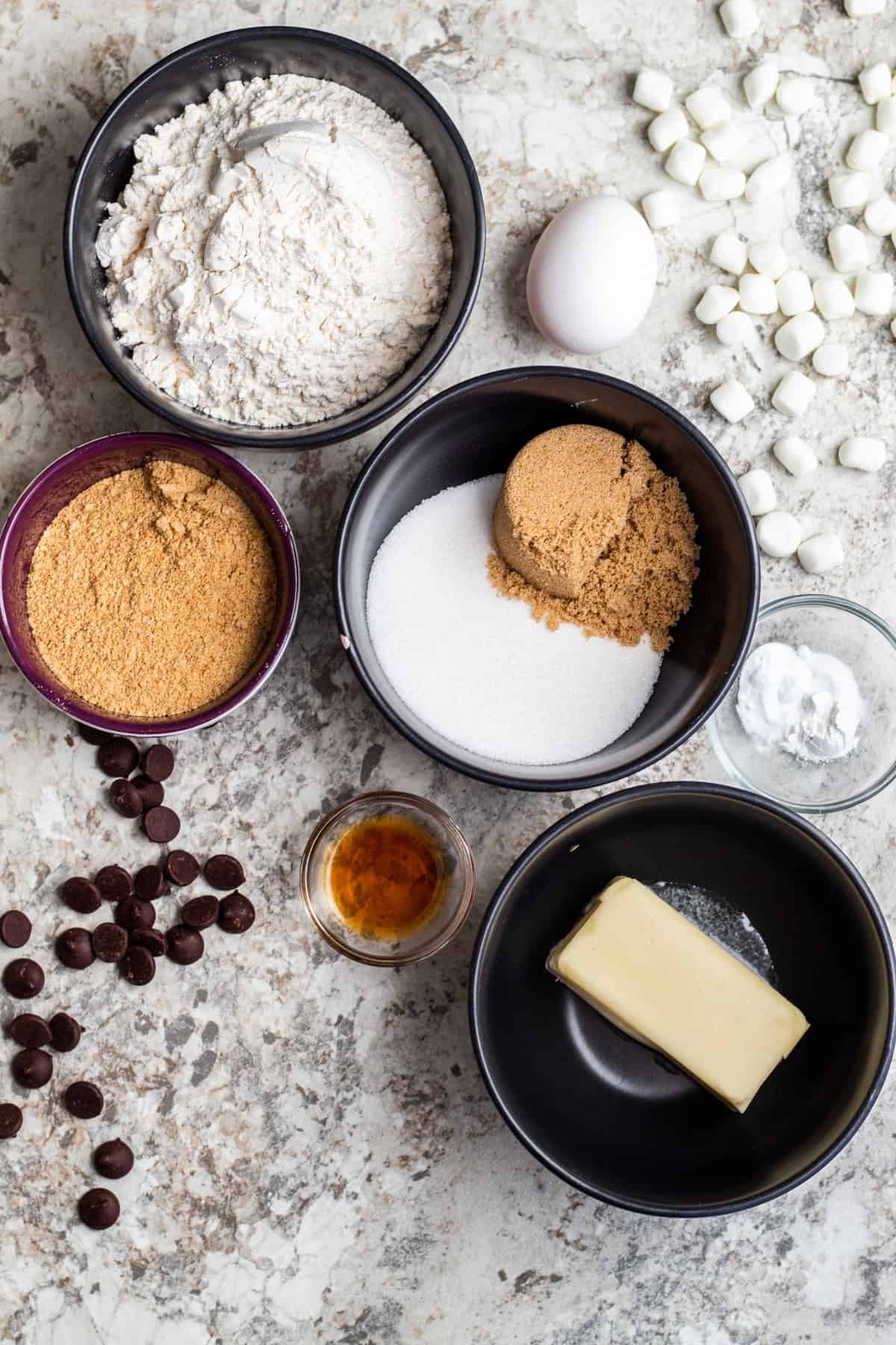 Overhead shot of s'mores cookie ingredients in small bowls on a white counter.