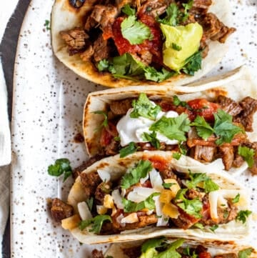 Overhead shot of tacos on a white serving tray.
