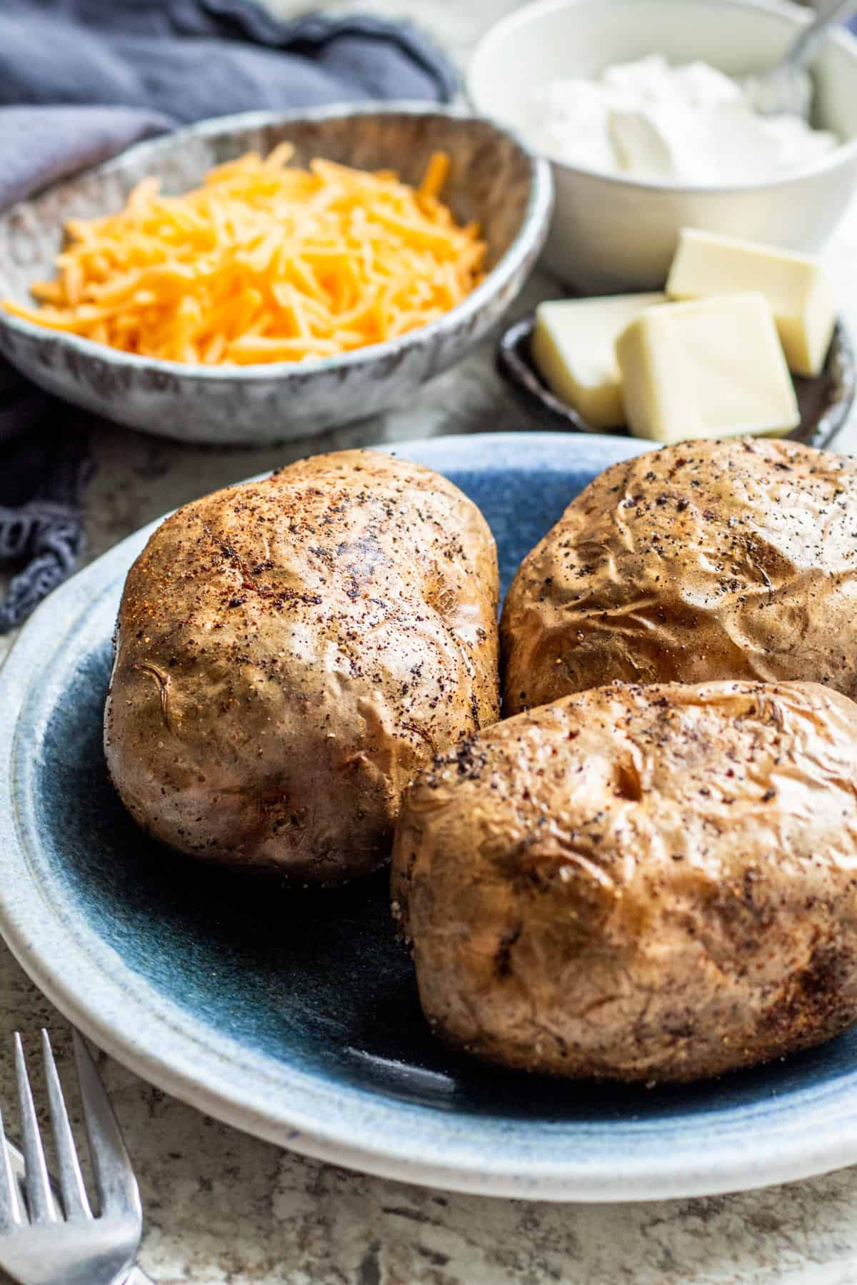 Baked potatoes on a blue plate with toppings in background.
