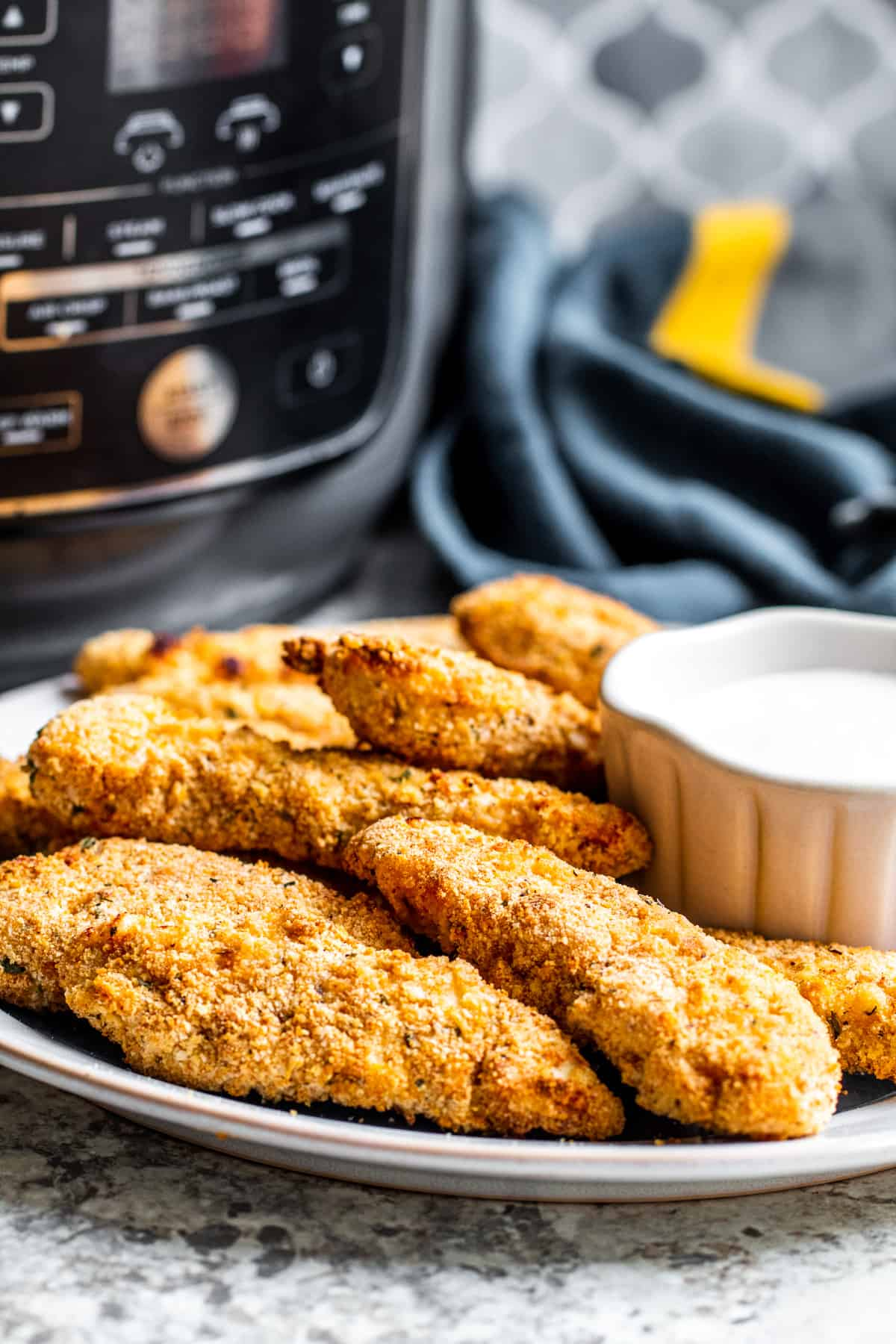 Chicken tenders on plate with sauce and air fryer in the background.