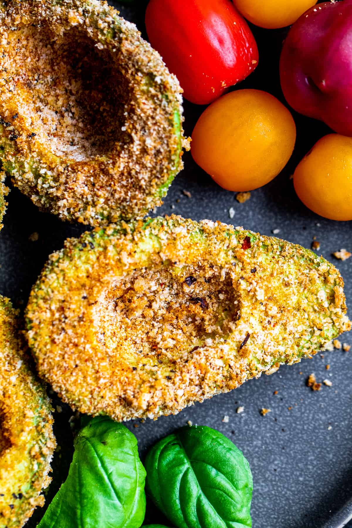 Overhead shot of breaded avocados on gray plate.