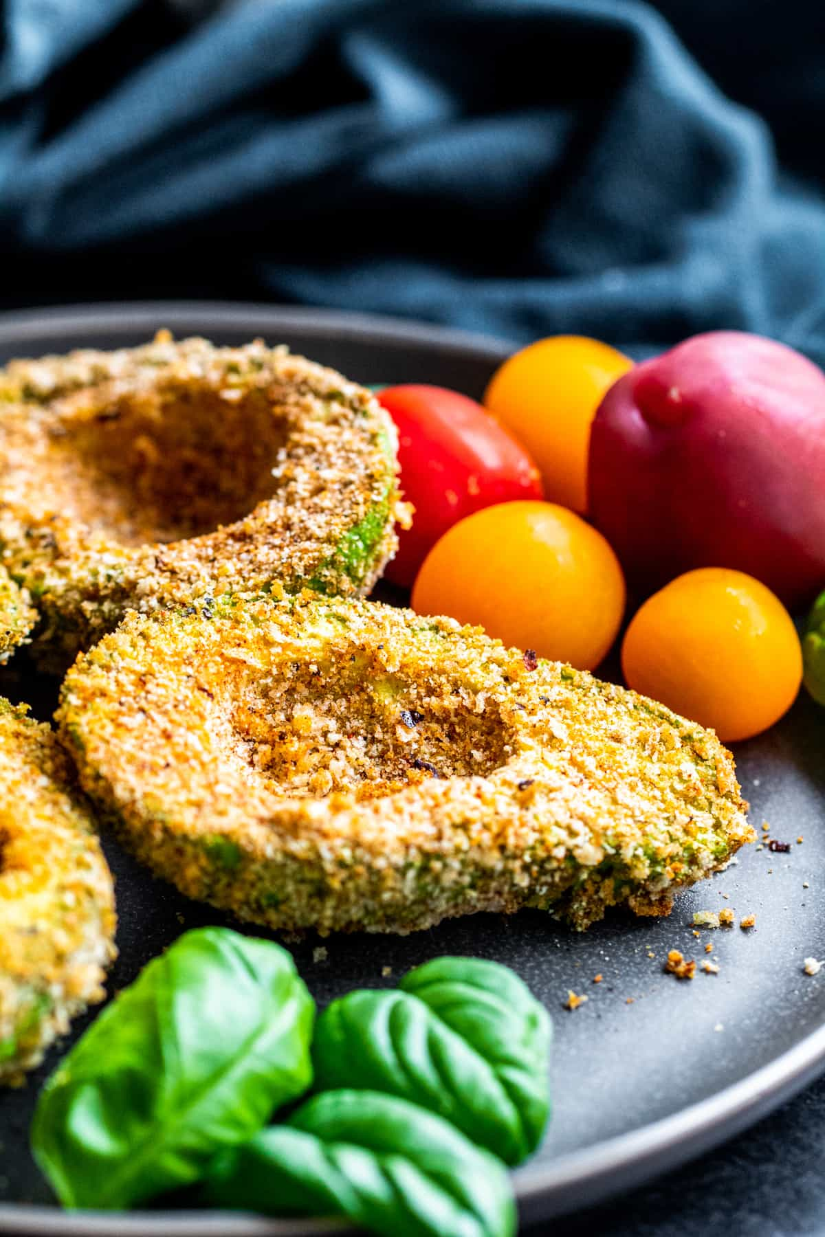 Angle shot of fried avocados on a gray plate with tomatoes and basil.