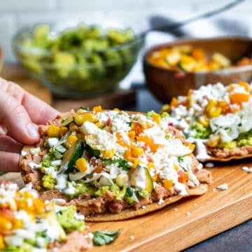 Hand picking up tostada off of cutting board.