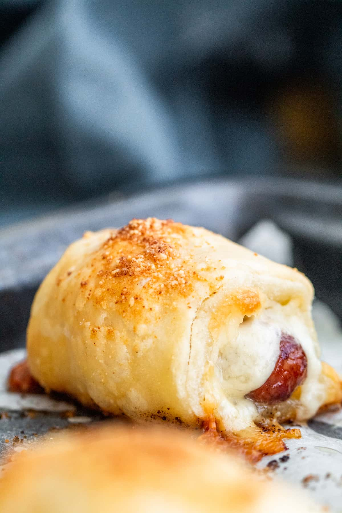 Close up show of pigs in a blanket with parchment paper.