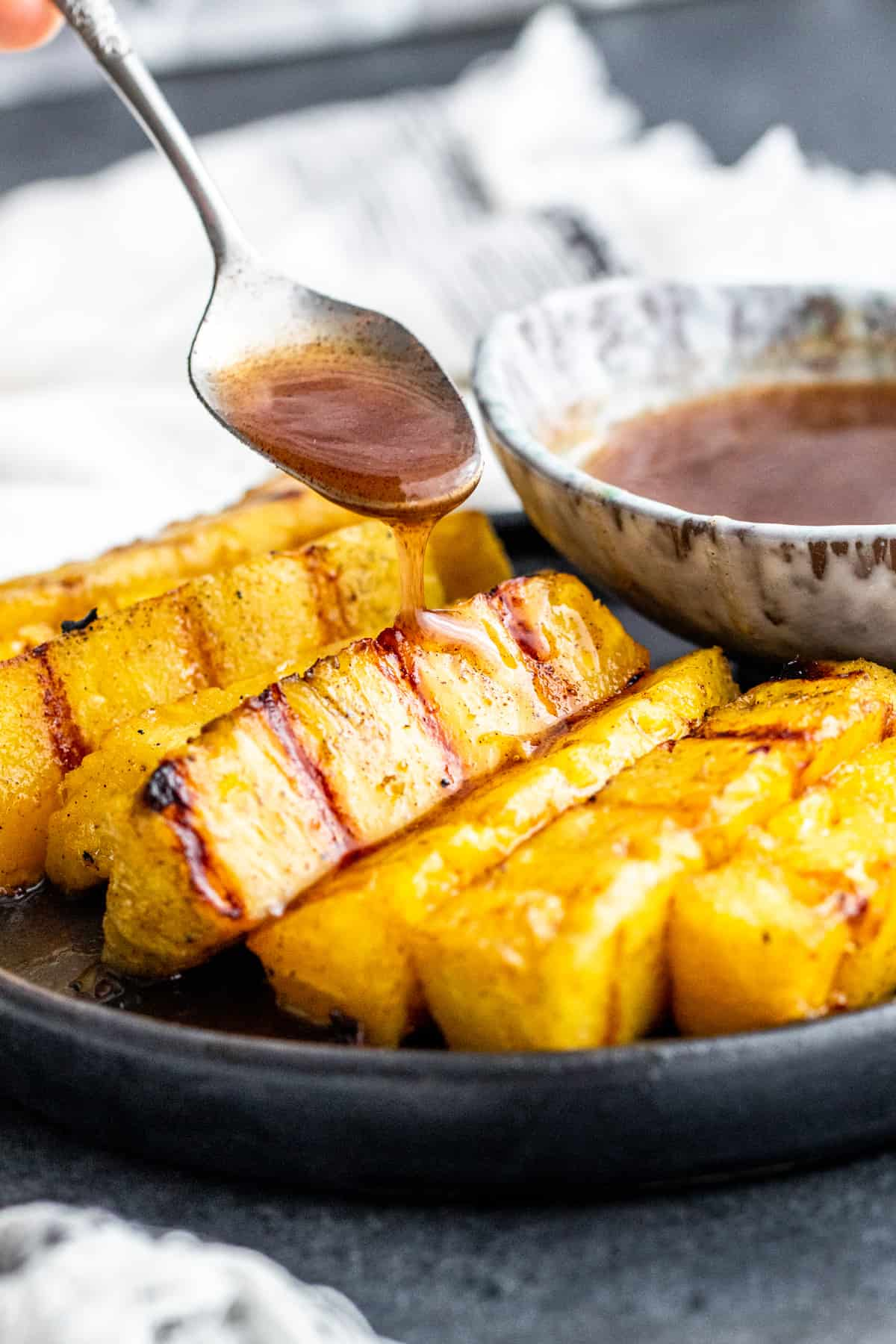 Hand using silver spoon to drizzle cinnamon sauce on cooked pineapple.
