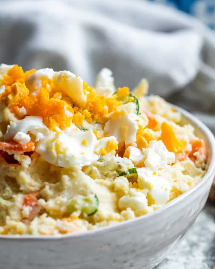 Close up angle of potato salad in white bowl.