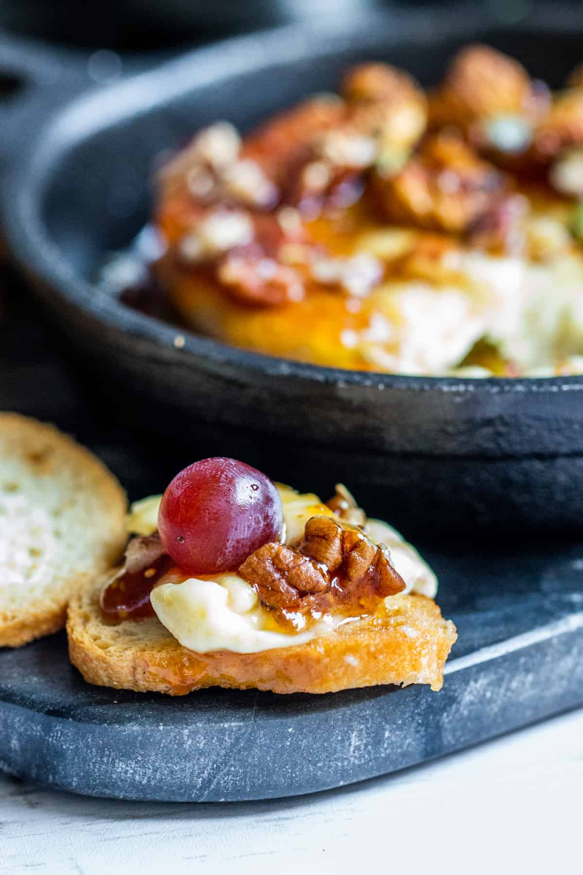 Cheese on bread with grape on top.