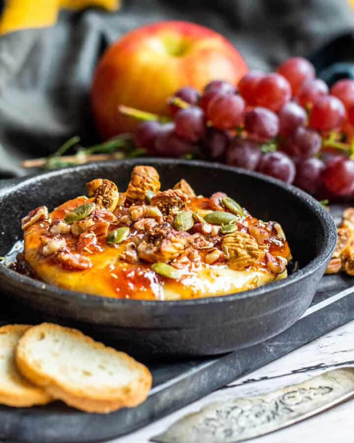 Brie in small cast iron skillet with grapes in the background.