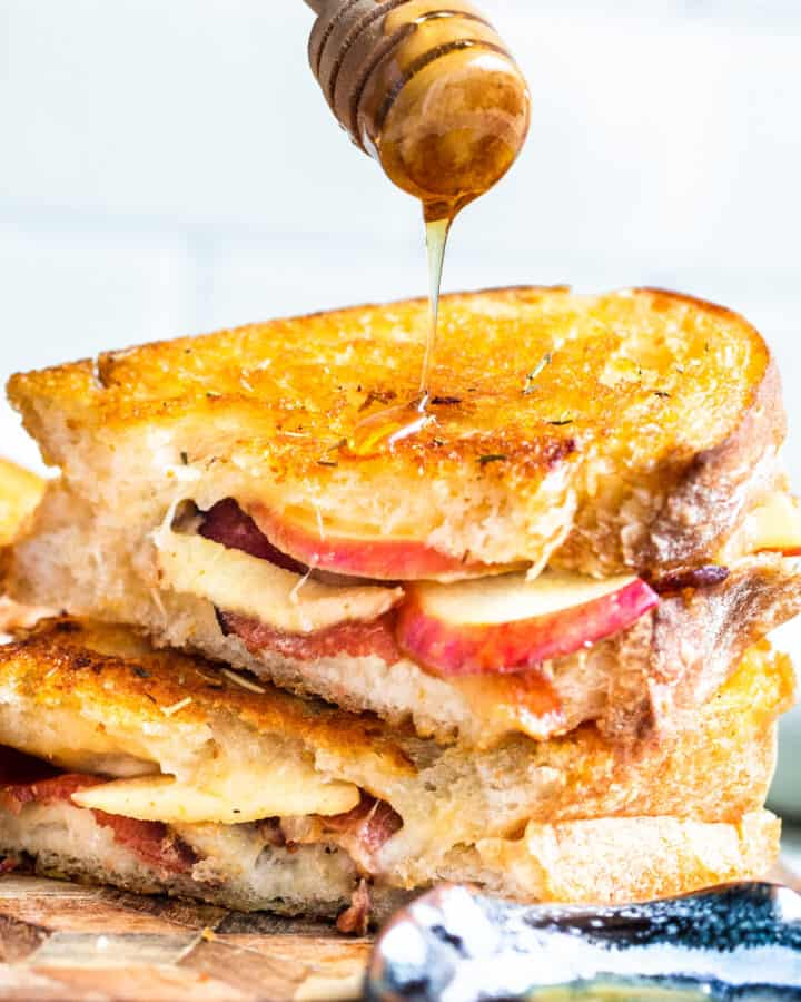Hand drizzling honey over top of stack of sandwiches.