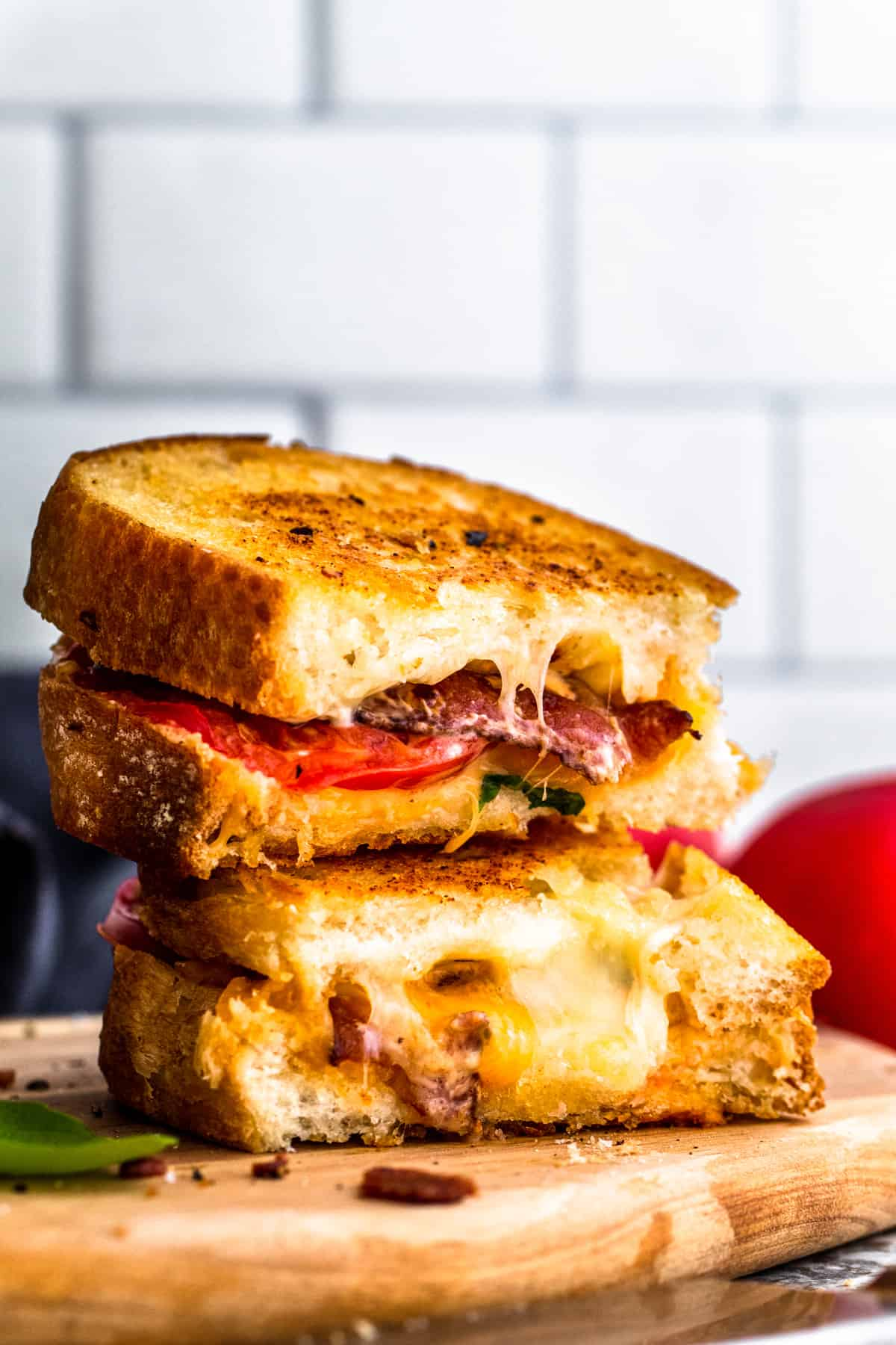 Stack of two bacon grilled cheese sandwiches on wooden cutting board.