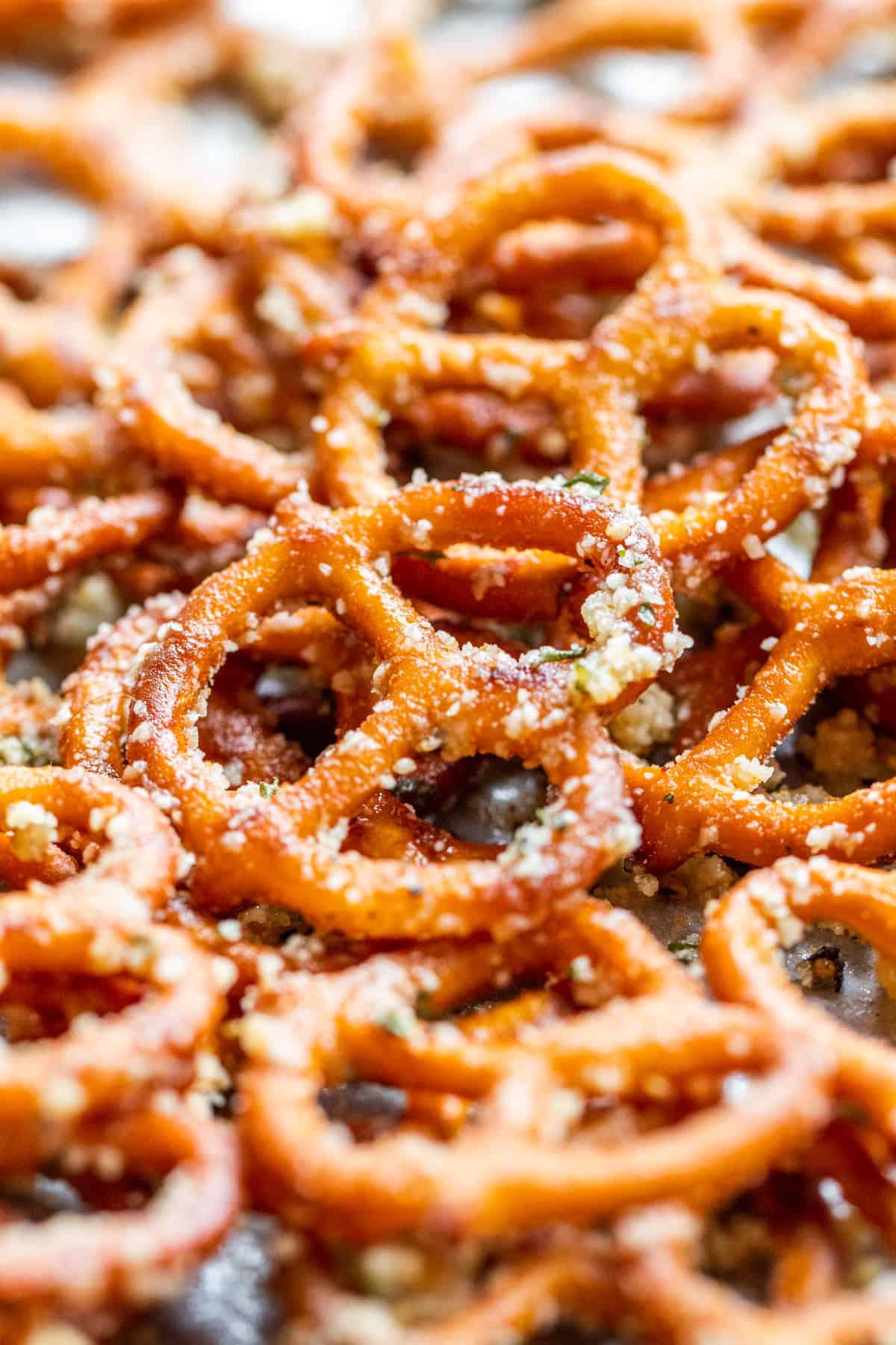 Close up shot of garlic parmesan pretzels on cookie sheet.