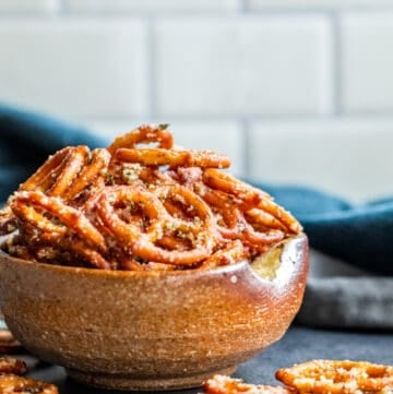 Pretzels in bowl with some fallen on table.