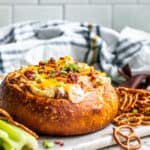 Baked dip in a bread bowl on white counter sitting on serving tray.