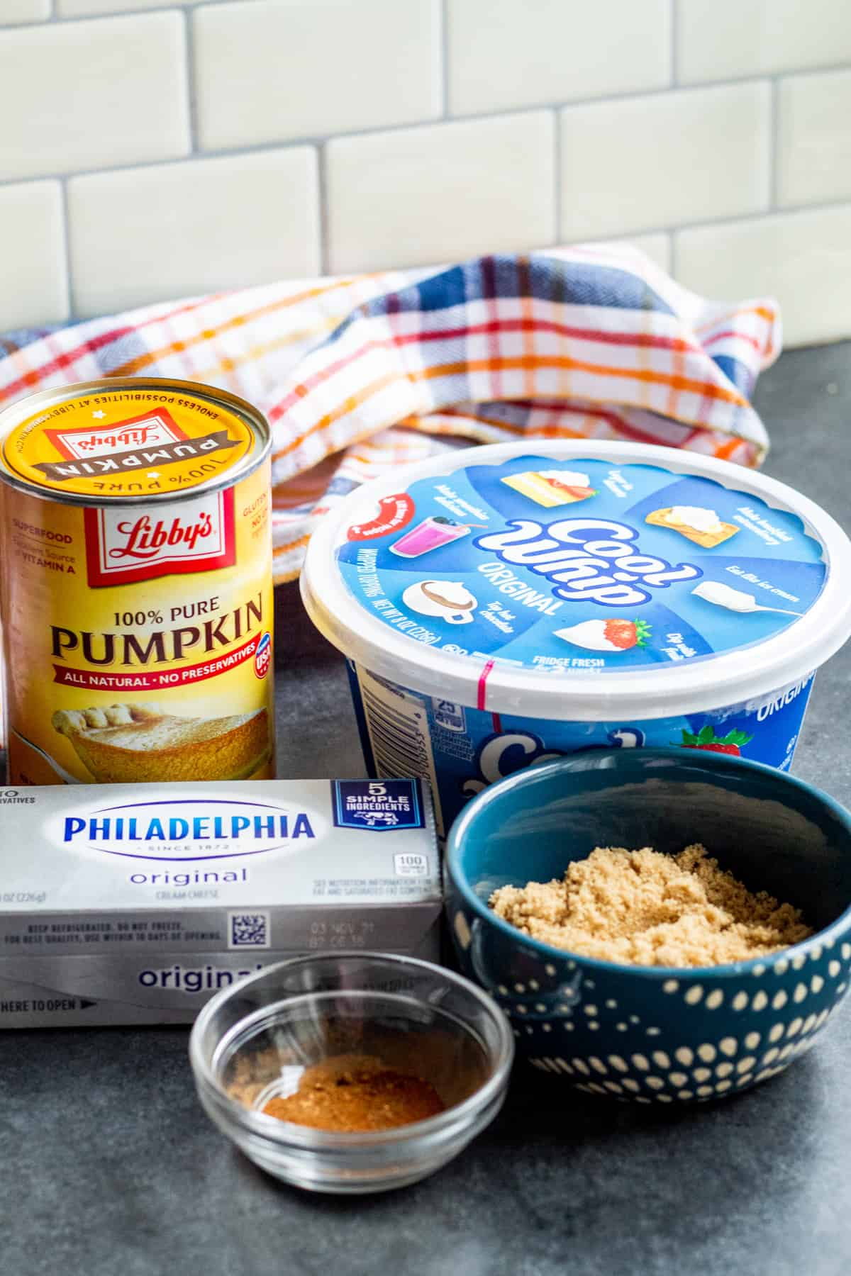 Pumpkin dip ingredients laid out on blue counter.