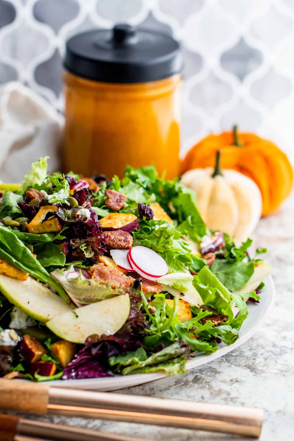 Salad on large plate with dressing and pumpkin in background.