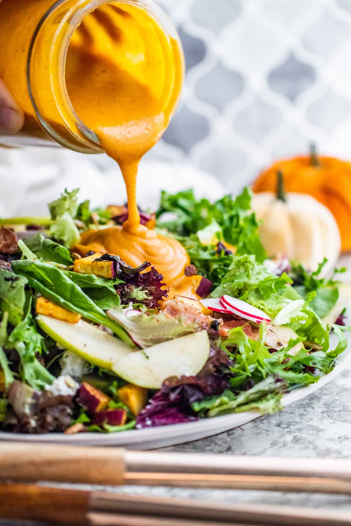 Hand pouring pumpkin dressing over greens.